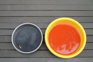 Natural dye in buckets; one blue, one orange.