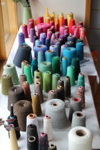 Colourful weaving threads on table.